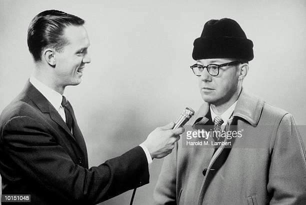 MAN WITH MICROPHONE INTERVIEWS A MAN