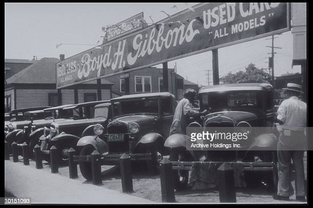 AFRICAN AMERICAN ATTENDANT CLEANS HOOD OF FORD