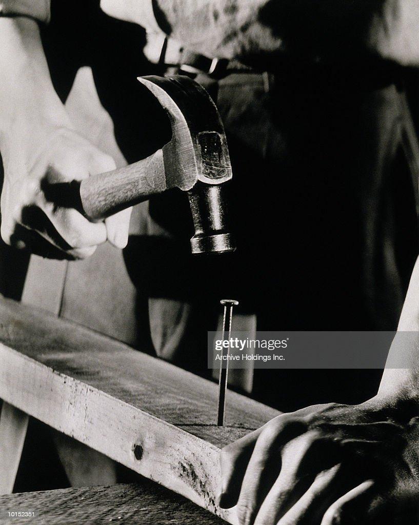 CLOSE UP OF MAN HAMMERING A LARGE NAIL : Stockfoto