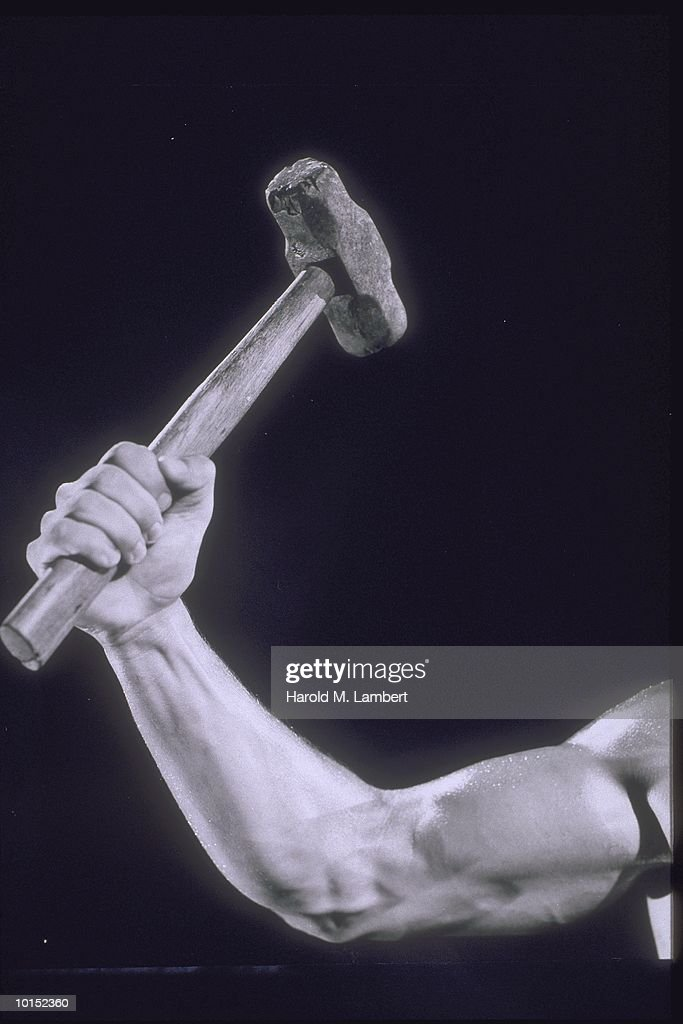 MUSCLED ARM RAISES SLEDGEHAMMER IN AIR : Stockfoto