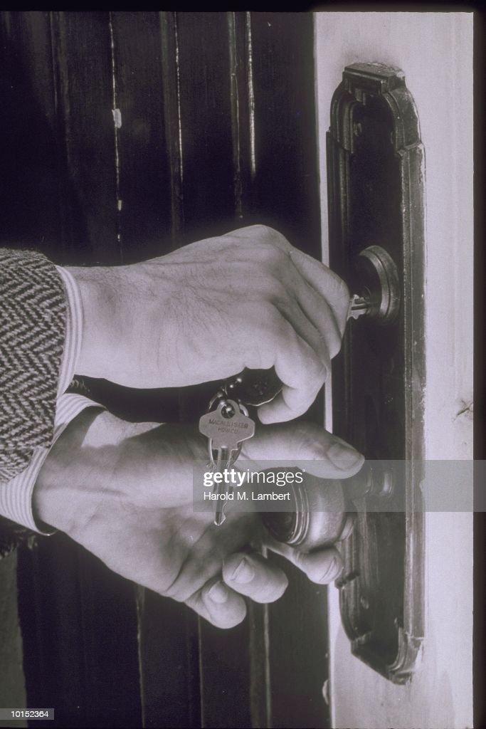 MANS HANDS UNLOCK A DOOR, 1940S : Stockfoto