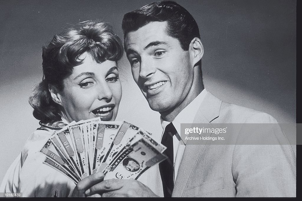COUPLE SMILING AT A SPREAD OF MONEY : Stockfoto