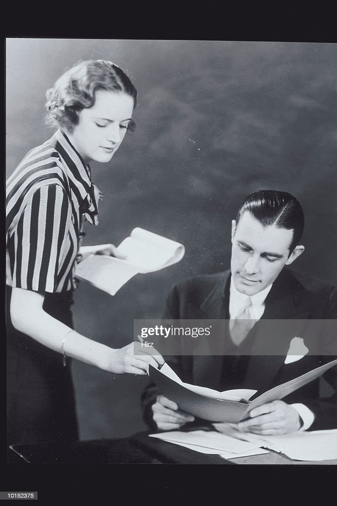 BUSINESS PEOPLE LOOKING AT PAPERS : Stockfoto