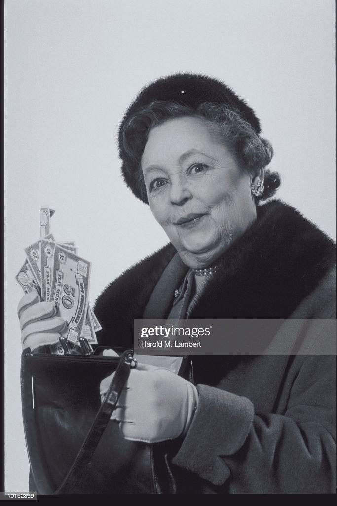 OLDER WOMAN PULLS CASH FROM POCKETBOOK : Stockfoto