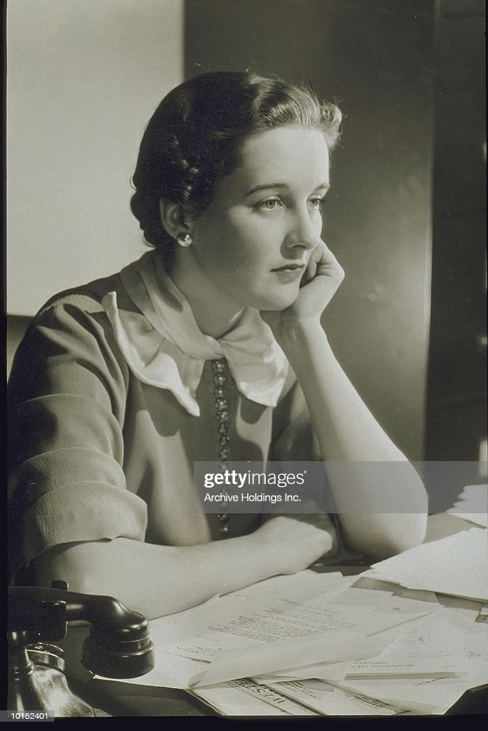 YOUNG WOMAN SEATED AT A DESK, CIRCA 1935 : Stockfoto