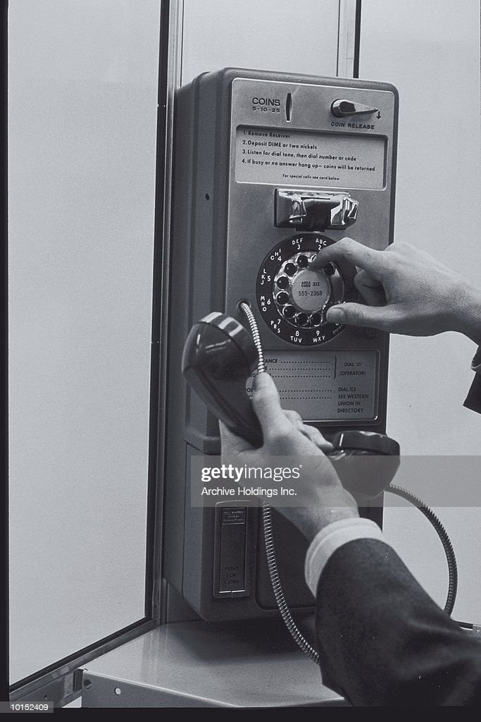 A PERSON DIALING A PAY PHONE : Stockfoto