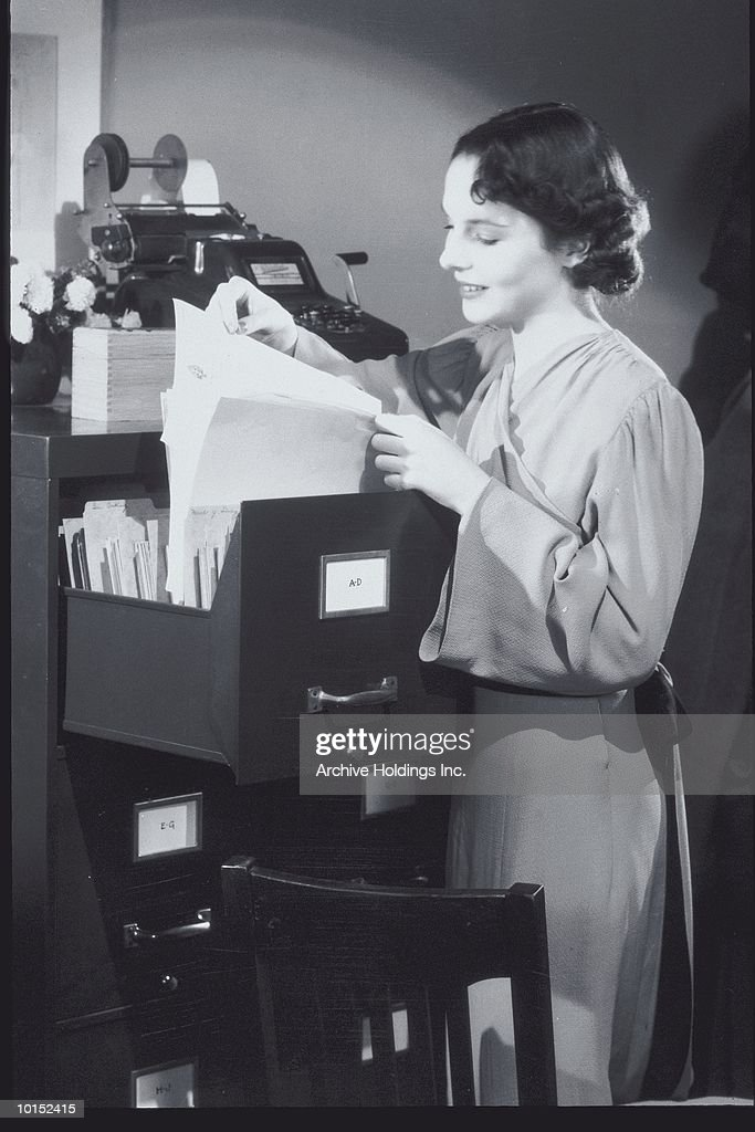 YOUNG WOMAN FILING IN AN OFFICE : Stockfoto
