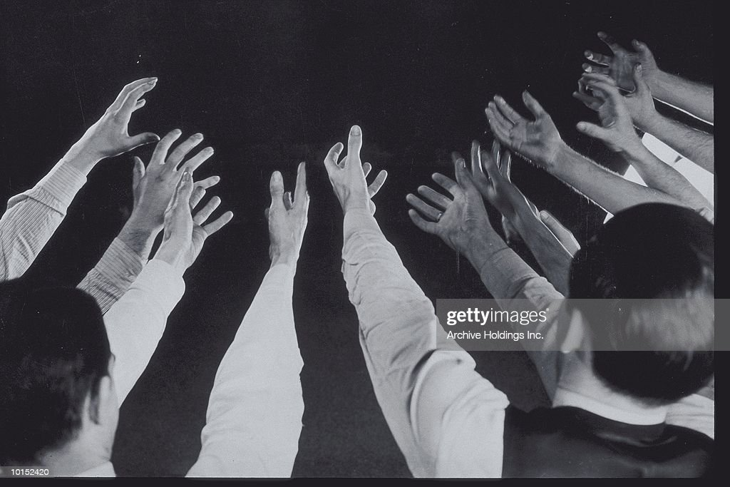 MENS HANDS REACHING OUT INTO BLACKNESS : Stockfoto