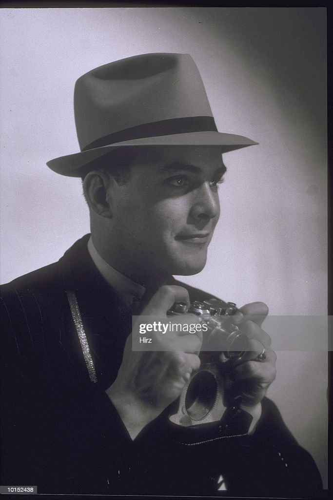PHOTOGRAPHER WITH CAMERA AND HAT, 1930S : Stockfoto