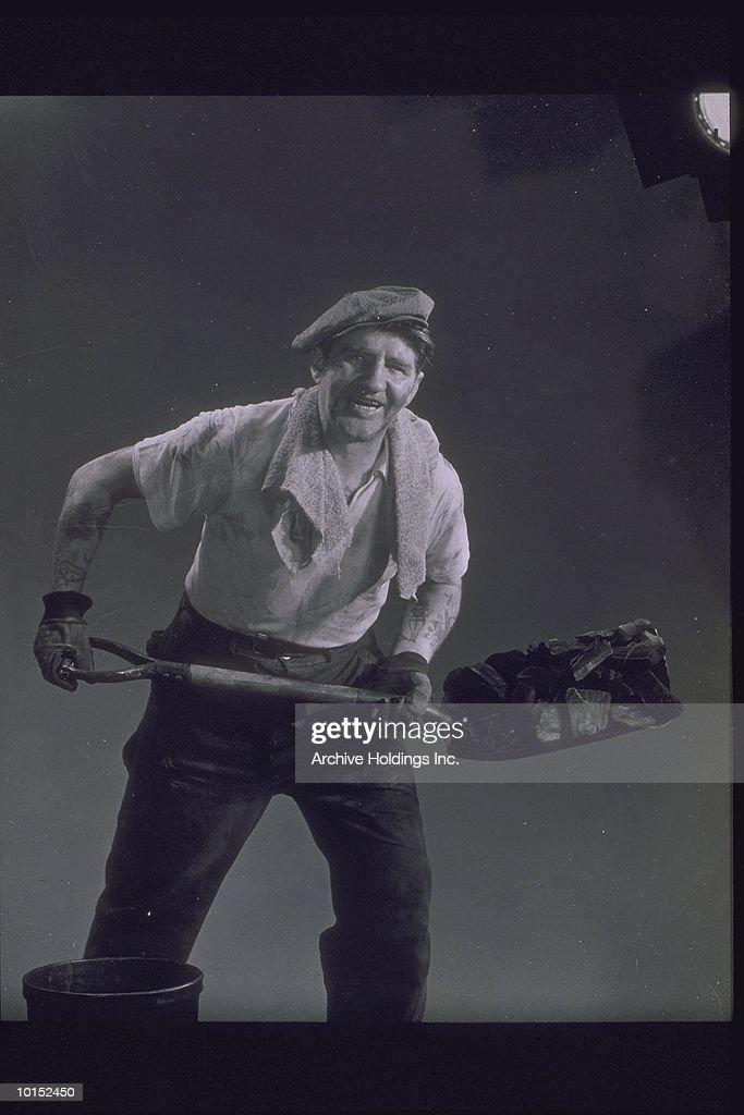 MAN IN WORK CLOTHES SHOVELS COAL, CIRCA 1930 : Stockfoto