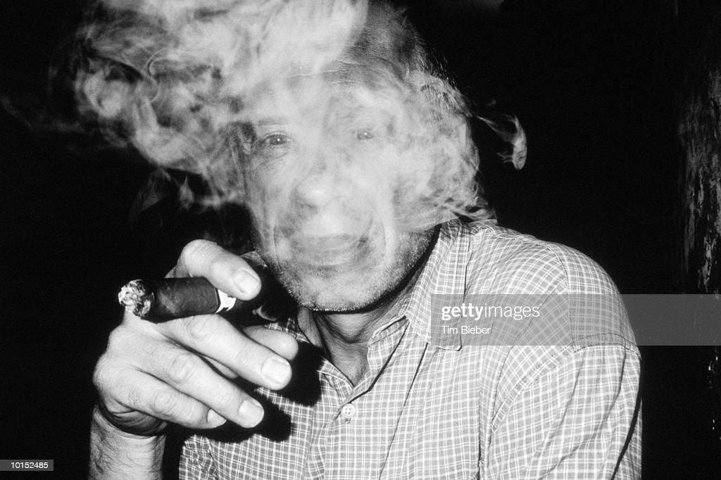 MAN SMOKING CIGAR : Stockfoto