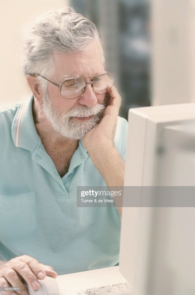 MATURE MAN USING PERSONAL COMPUTER : Stockfoto