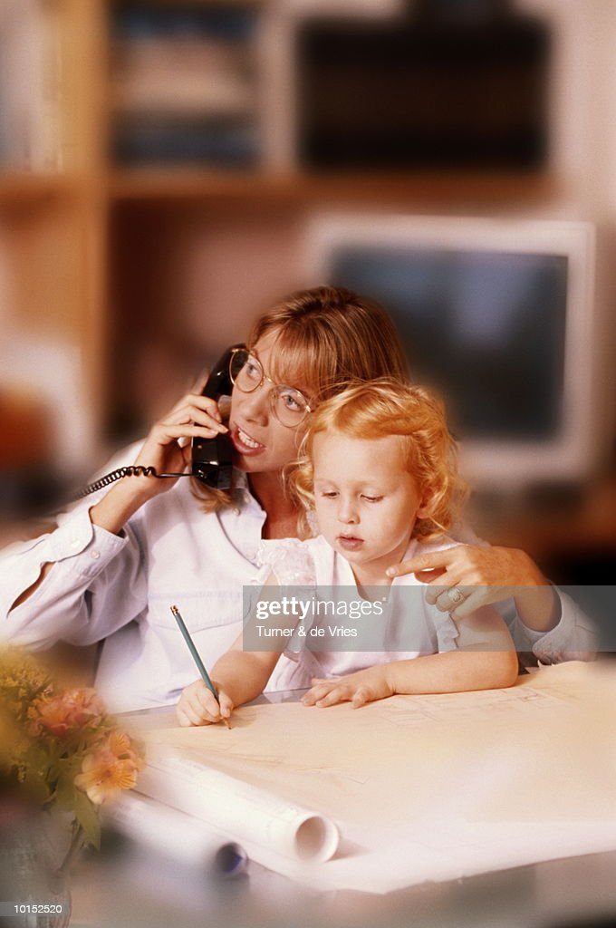 MOTHER ON PHONE WITH DAUGHTER ON HER LAP : Stockfoto