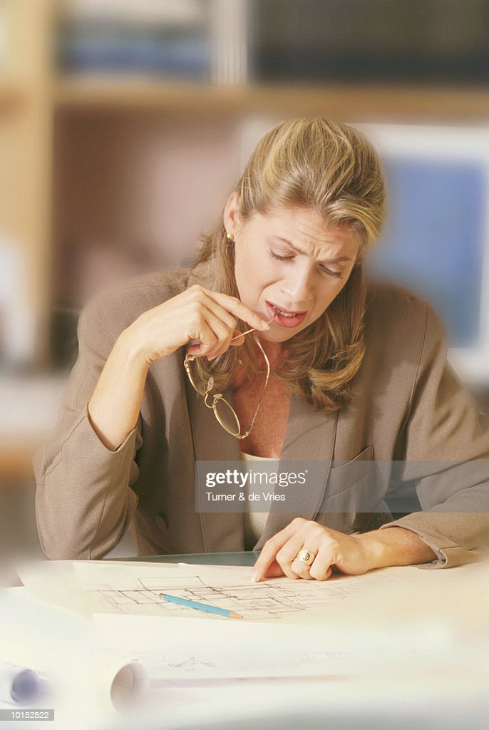 FROWNING BUSINESSWOMAN REVIEWING PLANS : Stockfoto