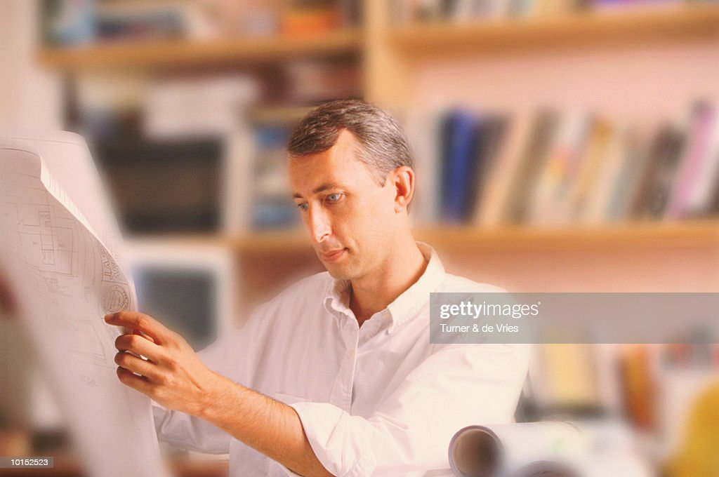 MAN REVIEWING PLANS : Stockfoto