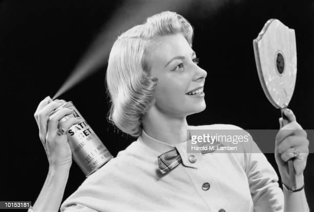 WOMAN APPLYING HAIR SPRAY, HAND MIRROR