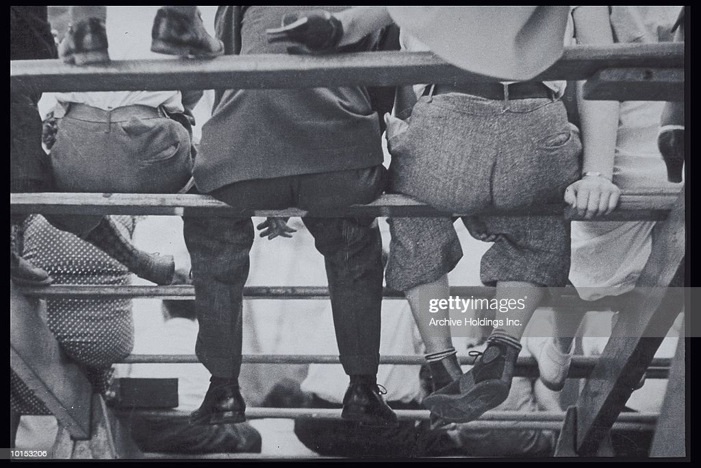 LEGS DANGLING FROM BLEACHER STEPS, 1940S : Stock Photo