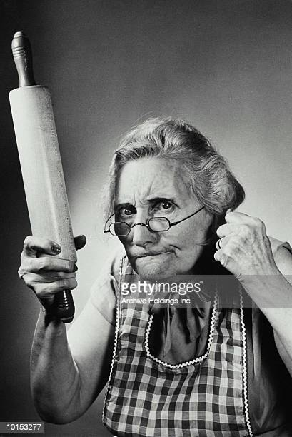 OLDER WOMAN HOLDING A ROLLING PIN