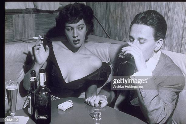 COUPLE DRINKING IN LOUNGE SETTING, 1950