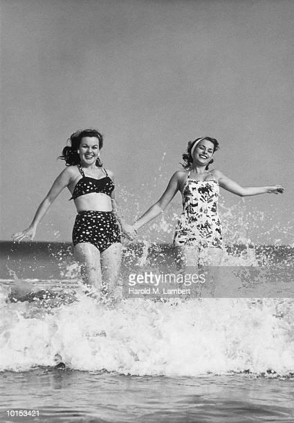 2 WOMEN IN SWIMSUITS, BEACH, 1950S