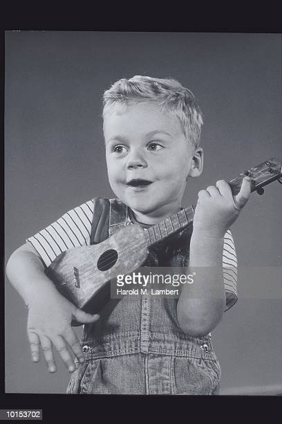 YOUNG BOY PLAYS FOUR STRING GUITAR, 1950