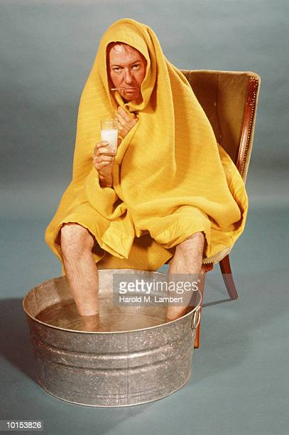 MAN WRAPPED IN BLANKET, FEET IN TUB