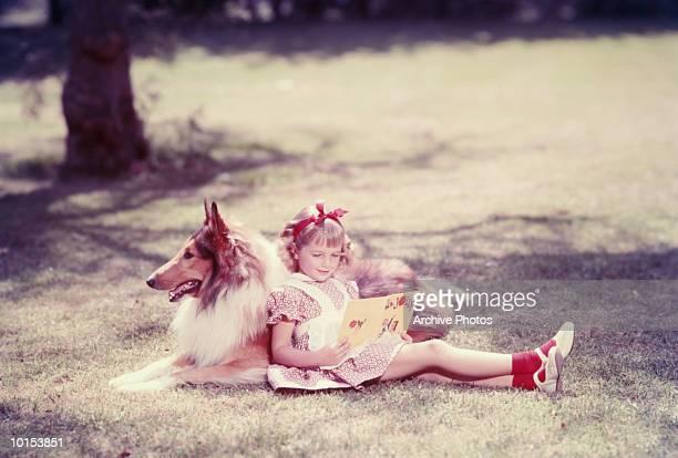 GIRL READS OUTSIDE LEANING AGAINST DOG