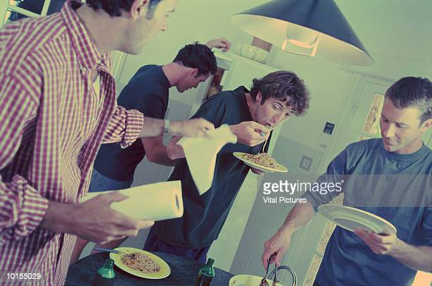 four men eating meal in kitchen, bachelors - cross processed stock pictures, royalty-free photos & images