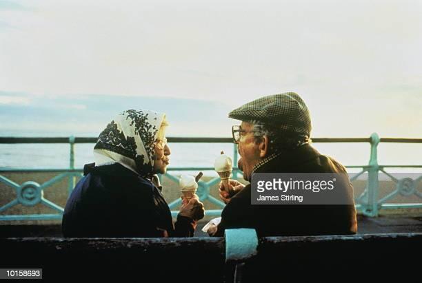 MATURE COUPLE EATING ICE CREAM, SEASIDE