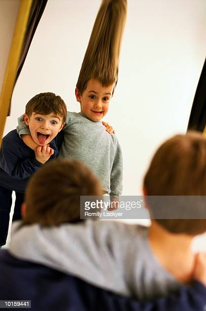 young boy looking in distorting mirror - fun house stock pictures, royalty-free photos & images