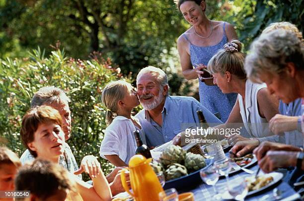 girl kisses grandpa at family barbecue table - 家族の集まり ストックフォトと画像