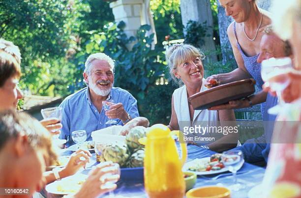 40-60 YEAR OLDS EATING OUTSIDE AT TABLE