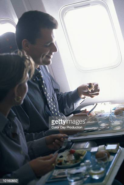 MAN AND WOMAN HAVING MEAL ON AIRPLANE
