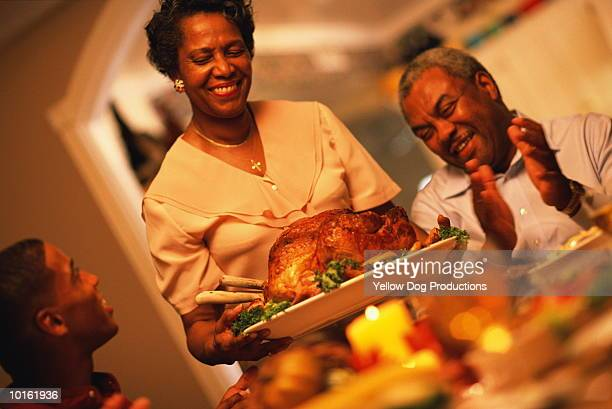 family holiday dinner, the turkey - african american christmas images stock pictures, royalty-free photos & images