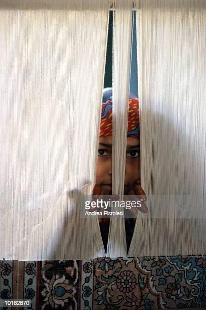 WOMAN PEEKING BETWEEN CARPET YARN, KASHMIR,