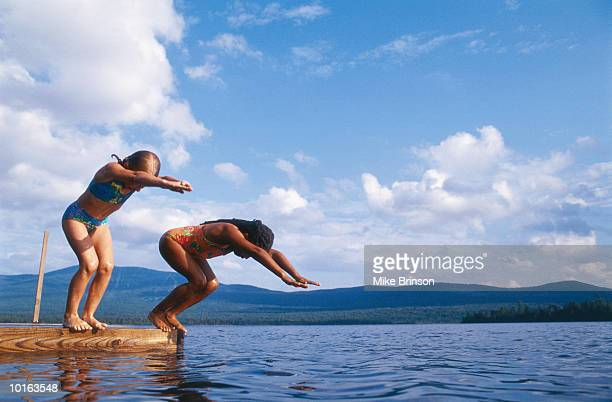 girls diving off dock, moosehead lake, maine - moosehead lake stock photos and pictures