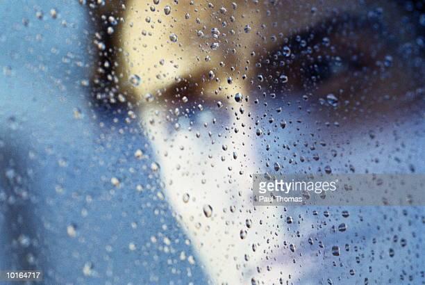 PORTRAIT OF MAN THROUGH WET WINDOW