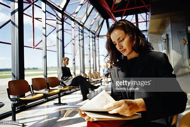 BUSINESSWOMAN AT AIRPORT READING PAPER
