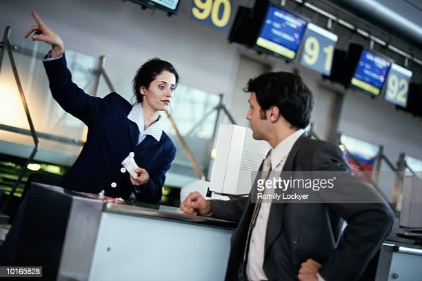 BUSINESSMAN CHECKING IN AT AIRPORT