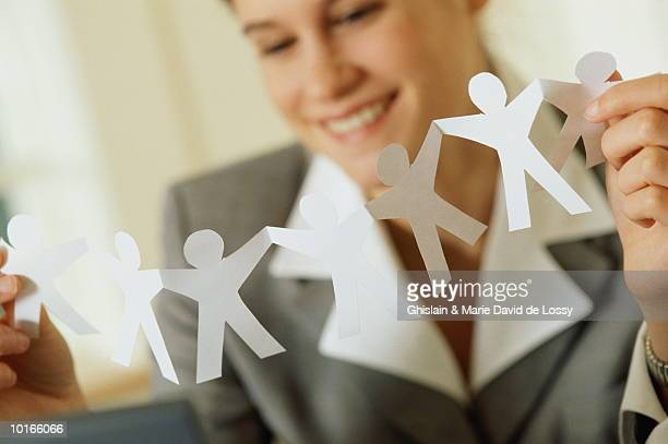 YOUNG BUSINESSWOMAN HOLDING PAPER DOLLS