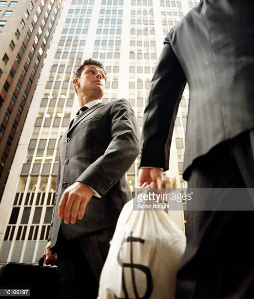 TWO BUSINESSMEN WITH MONEY BAGS