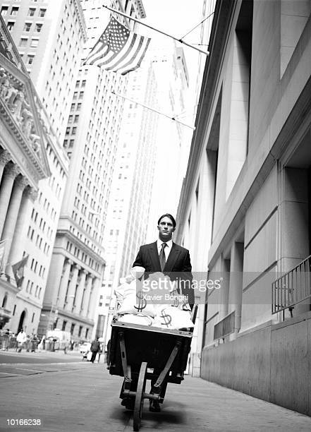 BUSINESSMAN WITH WHEELBARROW FULL OF MONEY