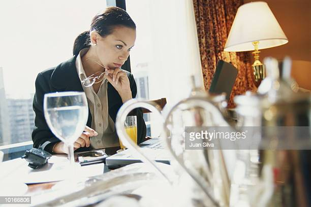 BUSINESSWOMAN EATING AND WORKING IN HOTEL ROOM
