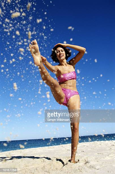 YOUNG WOMAN KICKING SAND IN AIR