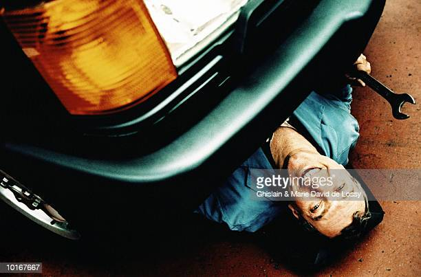 car mechanic with wrench, under car - sotto foto e immagini stock
