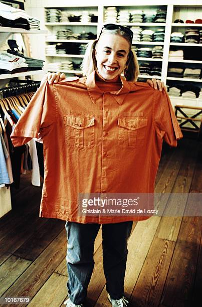 WOMAN HOLDING BIG RED SHIRT IN SHOP