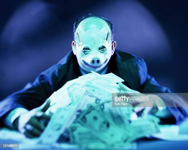 man with pig mask on hoarding money - los siete pecados capitales fotografías e imágenes de stock