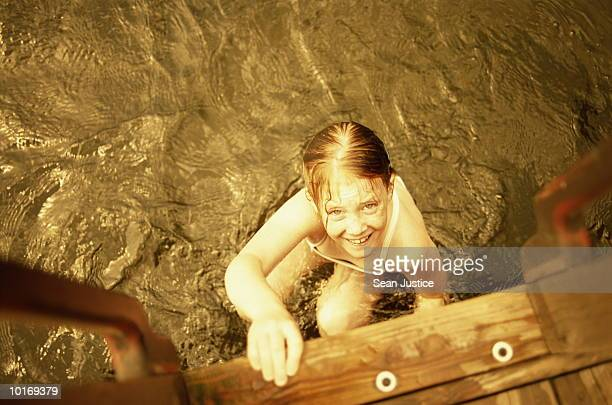 YOUNG GIRL CLIMBING OUT OF LAKE