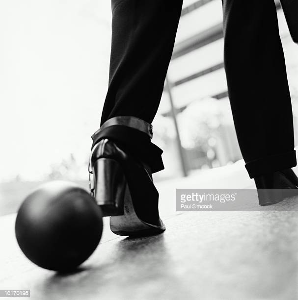 BUSINESSWOMAN WITH BALL AND CHAIN, WALKING