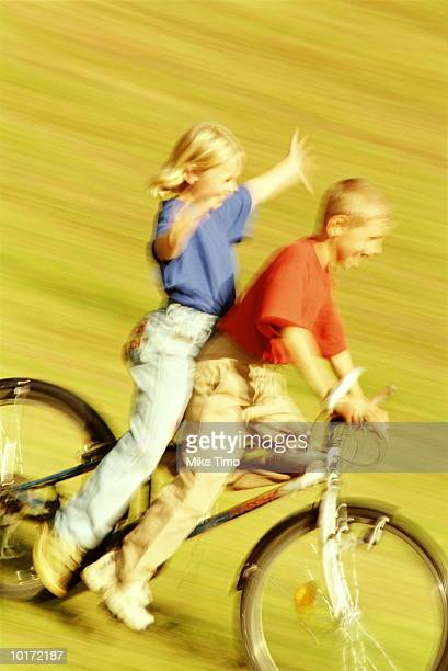 girl and boy riding on mountain bike - hands free cycling stock pictures, royalty-free photos & images
